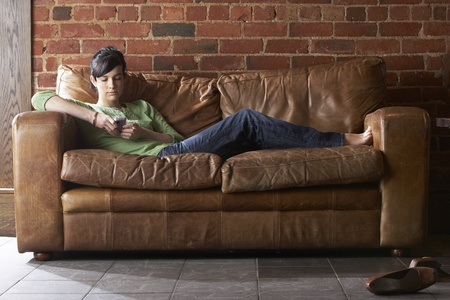 Young woman with phone on sofa photo