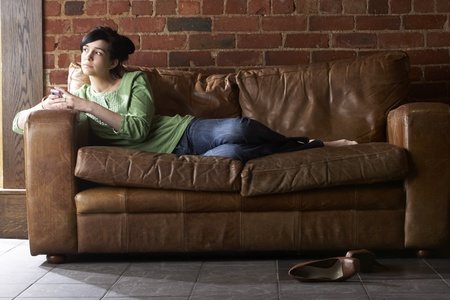 couch: Young woman with phone on sofa