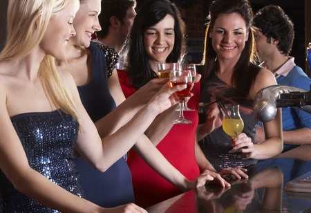 sideview: Young women drinking at bar