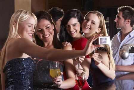 Young women drinking at bar photo