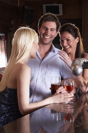 coquetear: Amigos riendo en el bar Foto de archivo