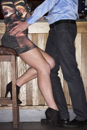 vertical bars: Young couple flirting at bar