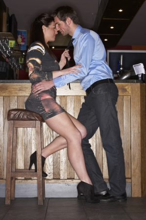 vertical bars: Young couple flirting at bar