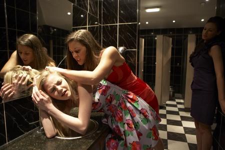 Two women having a fight in bathroom photo