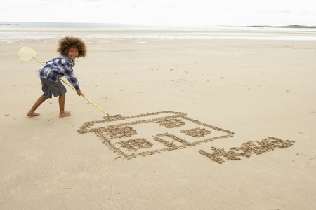 sand drawing: Boy drawing in sand Stock Photo