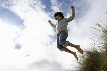 10 year old: Boy jumping over dune Stock Photo