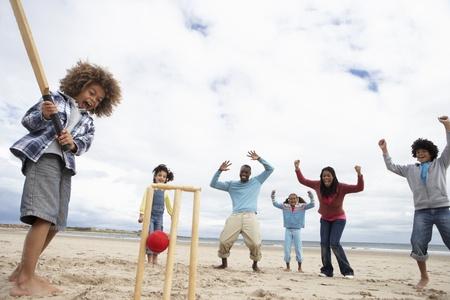 cricket ball: Family playing cricket on beach Stock Photo