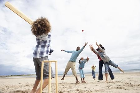 at bat: Familia jugando al cricket en la playa
