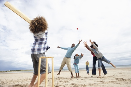cricket ball: Family playing cricket on beach Stock Photo
