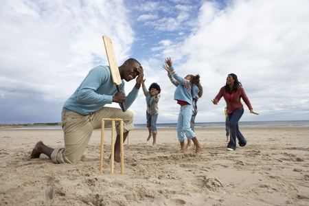 Family playing cricket on beach photo