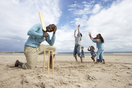 families together: Family playing cricket on beach Stock Photo