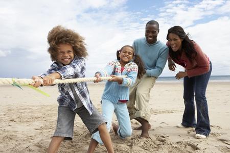 familia de cinco: Familia jugando tira y afloja en la playa Foto de archivo