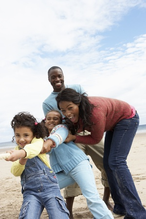 5 6 years: Family playing tug of war on beach
