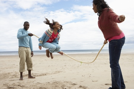skipping: Family playing on beach