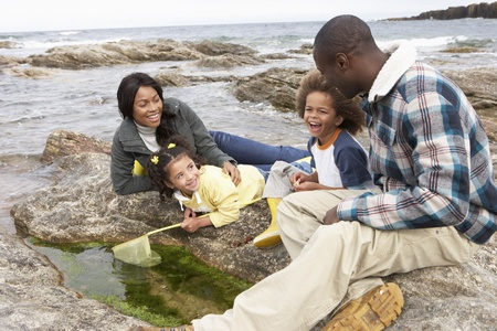 experiencing: Young family with fishing net on rocks Stock Photo