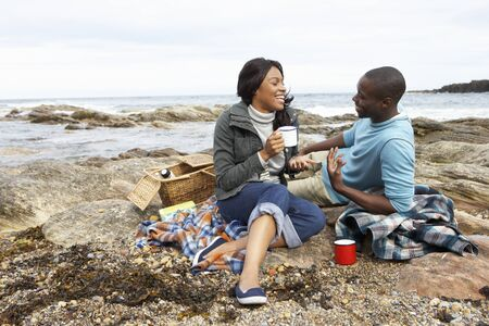 Couple having picnic on beach Stock Photo - 10361427