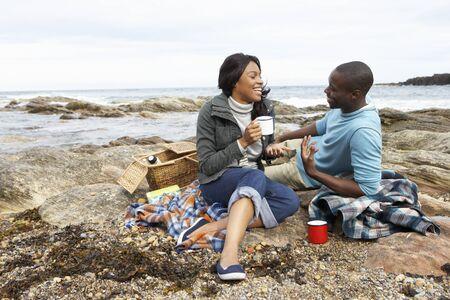 Couple having picnic on beach Stock Photo - 10361427