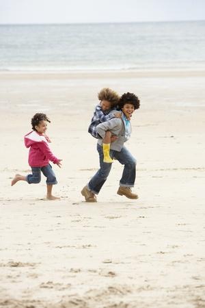 hermanos jugando: Niños felices jugando superpuesta en playa