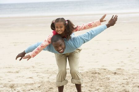 imitating: Father and daughter playing on beach