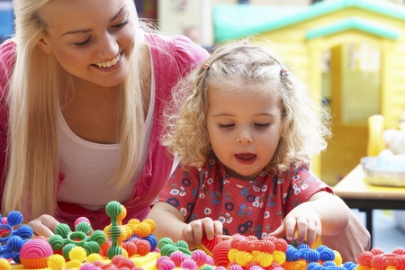 daycare: Young woman playing with girl