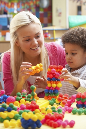 daycare: Young woman playing with boy