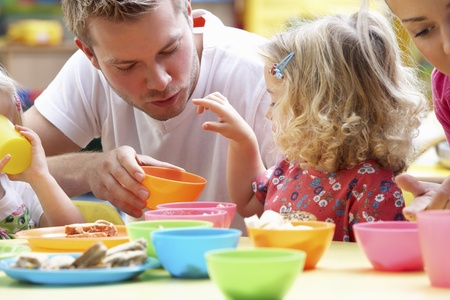 nursery school: Man with children playing together