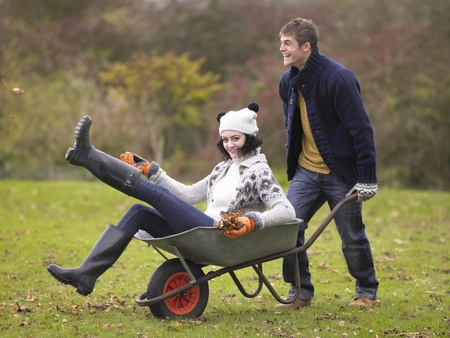 looking at each other: Young couple playing in wheelbarrow Stock Photo