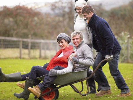 Two young couples playing in wheelbarrow photo