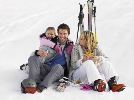 Jeune famille avec pique-nique en vacances de ski
