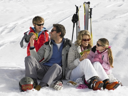 Jeune Famille Partage un pique-nique de vacances de ski