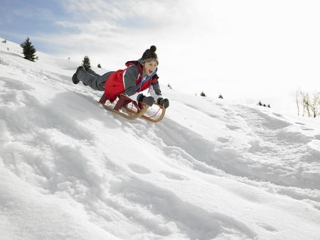 preteen boy: Pr�-ado gar�on sur un tra�neau dans la neige Banque d'images