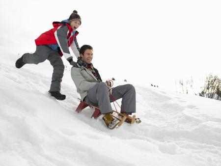 sledding: Young Father And Son Sledding