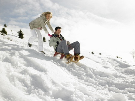 Young Couple Sledding Stock Photo
