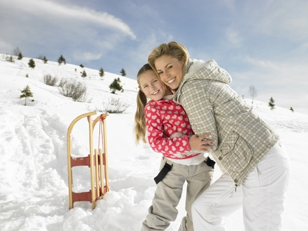 sledging people: Young Mother And Daughter On Winter Vacation Stock Photo
