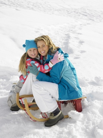 Young Mother And Daughter With A Sled In The Snow photo