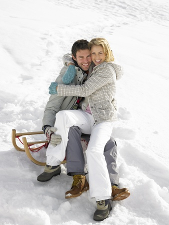 on lap: Young Couple On A Sled