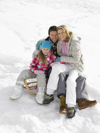 Young Family Sitting On A Sled In The Snow photo