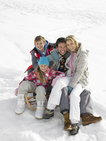 on lap: Young Family Sitting On A Sled In The Snow Stock Photo