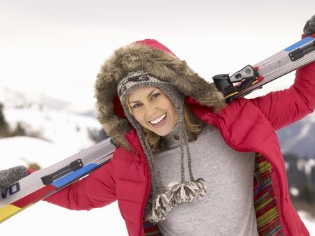Jeune femme tenant Skis Dans Paysage alpin Banque d'images