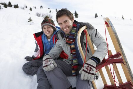 Young Father And Son In Snow With Sled photo