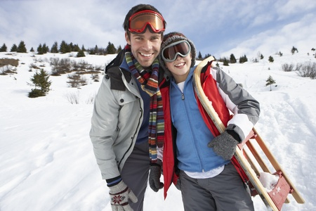 sledding: Young Father And Son In Snow With Sled