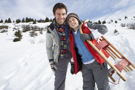 boy 12 year old: Young Father And Son In Snow With Sled