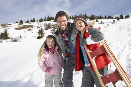 Young Father And Children In Snow With Sled photo