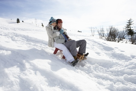 toboggan: Young Couple Sledding Stock Photo