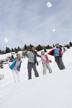 family fight: Young Family Throwing Snowballs On Winter Vacation Stock Photo