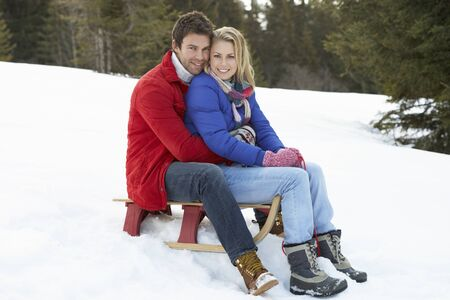 Young Couple On A Sled  In Alpine Snow Scene photo
