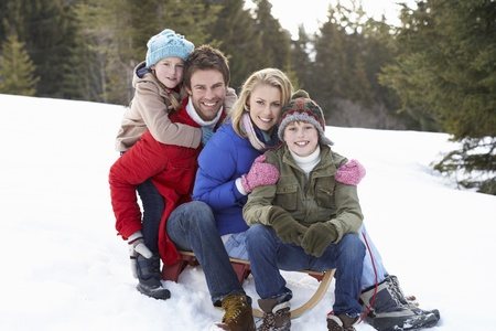 good looking boy: Young Family Sitting On A Sled In The Snow Stock Photo