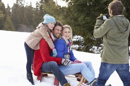 Jeune famille Assis sur un traîneau dans la neige