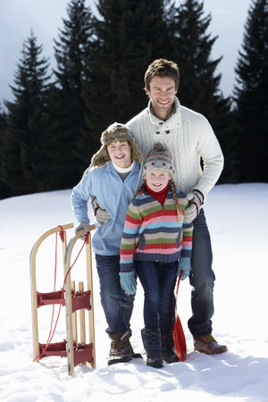 boy 12 year old: Young Father And Children In Snow With Sled