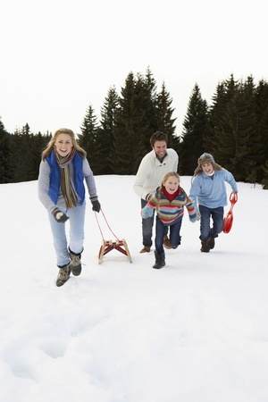 Young Family Running Through Snow With Sled photo